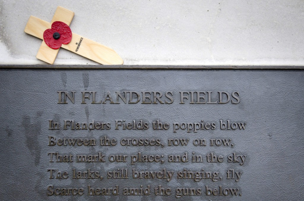In this photo taken on Nov. 12, 2013, a red poppy on a wooden remembrance cross lays above a bronze plaque which contains the poem In Flanders Fields by World War I Canadian soldier John McCrae at the Essex Farm Commonwealth Cemetery on in Ypres, Belgium. (AP Photo/Virginia Mayo)