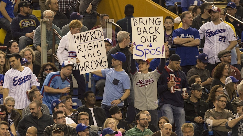 Fans hold up signs as the Toronto Blue Jays face the Cincinnati Reds in Grapefruit League play Friday, April 3, 2015 in Montreal. (CP Photo)