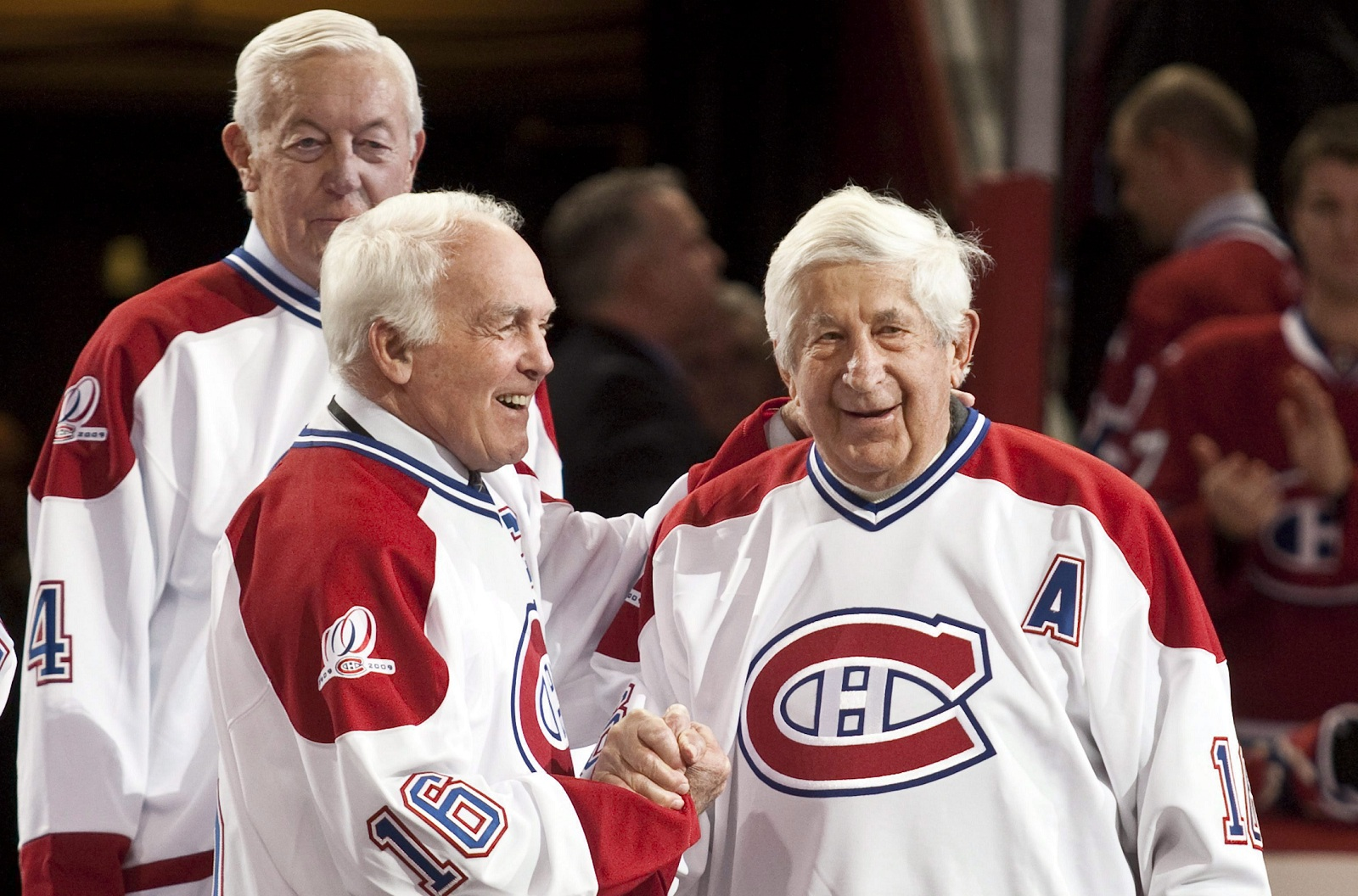 Former Montreal Canadien Henri Richard greets Elmer Lach, right as Jean Beliveau, rear, looks on during NHL centennial celebrations in 2009