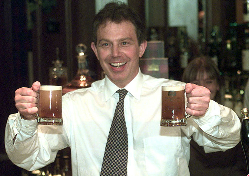 """Labour leader Tony Blair holds up half-pints of """"Blair Brew"""", a beer made especially for the election. (Ian Waldie/Reuters)"""