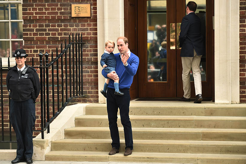 Prince George held by his father, Prince William, at the hospital to see his new sister on May 2, 2015 by Leon Neal/Afp/Getty Images