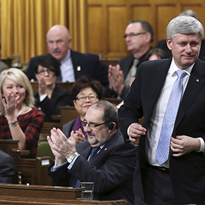 Canada's Prime Minister Stephen Harper stands to vote in the House of Commons on Parliament Hill in Ottawa March 30, 2015. Parliamentarians voted to expand Canada's military mission against Islamic State by launching air strikes against the militants' safe havens in Syria as well as Iraq. Chris Wattie/Reuters