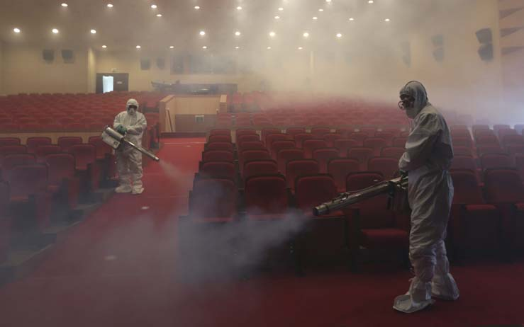 Workers in protective gear spray antiseptic as a precaution against the spread of MERS, Middle East Respiratory Syndrome, at an art hall in Seoul, South Korea. The outbreak has caused panic in the East Asian country. (Lee Jin-man/AP)