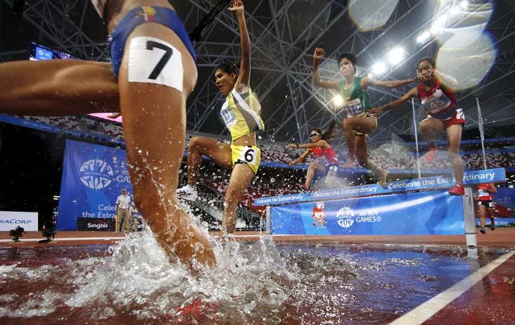 Contestants jump into the water pit during the women's 3,000-m steeplechase finals at the Southeast Asian Games in Singapore (Edgar Su/Reuters)