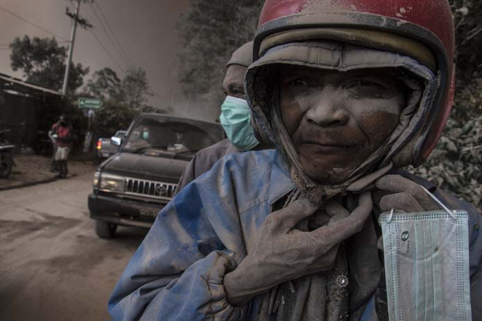 A motorcyclist is covered by ash spewed by the Mount Sinabung volcano in North Sumatra, Indonesia. Nearly 3,000 people were evacuated from their homes after the country upgraded the threat posed by the volcano to the highest possible level. (Sutanta Aditya/AFP/Getty Images)