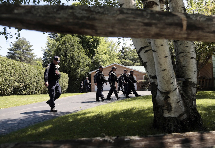 Corrections officers walk through a residential area during a search for two escaped prisoners from Clinton Correctional Facility, on Wednesday, June 24, 2015, in Malone, N.Y. Hundreds of searchers checked ATV trails and logging roads and went door-to-door in far northern New York trying to close in on David Sweat and Richard Matt, who escaped from the maximum-security prison more than two weeks ago. (AP Photo/Mike Groll)