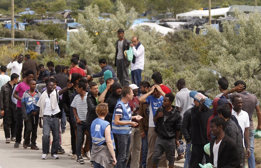 """Migrants queue to receive their daily food distribution in a makeshift camp known as the """"jungle"""", in Calais, northern France, Thursday, June 25, 2015. Migrants from Sudan, Eritrea and elsewhere are camped by the thousand in the port city of Calais trying to reach Britain, where they believe they will have better job prospects. (AP Photo/Michel Spingler)"""