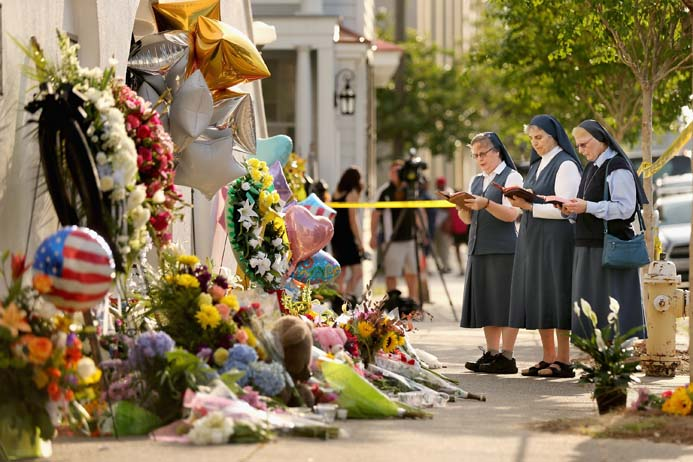 Nuns from the Order of the Daughters of St. Paul pray outside the Emanuel African Methodist Episcopal Church in Charleston, S.C., after nine people were shot dead inside it during a prayer meeting on Wednesday night. South Carolina Gov. Nikki Haley called for the death penalty for Dylann Storm Roof, 21, of Lexington, S.C., if he is found guilty of murdering them. Among the dead is Rev. Clementa Pinckney, the pastor of the church, which is the oldest black congregation in America south of Baltimore. (Photo by Chip Somodevilla/Getty Images)