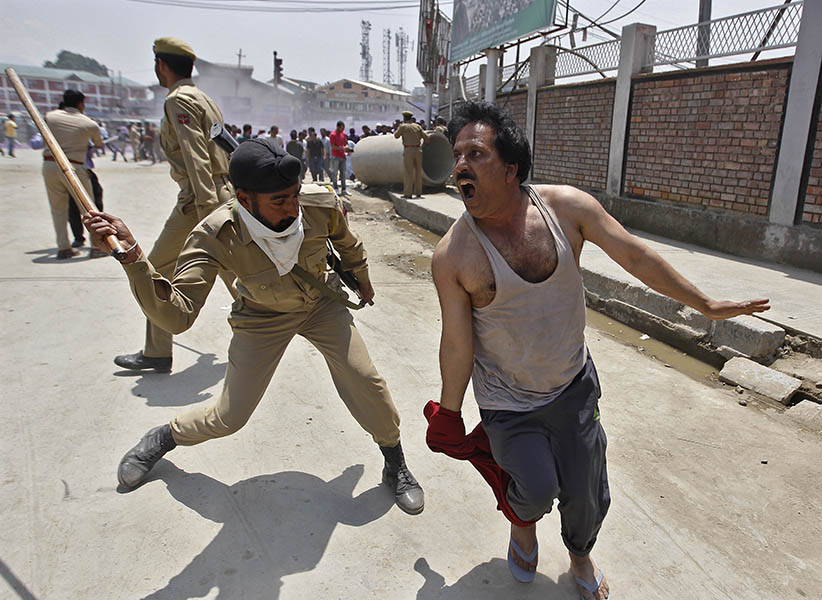 Brute force: A policeman in Srinagar, India, attacks a government employee demanding overdue pay and a regularization of temporary jobs (Danish Ismail/Reuters)