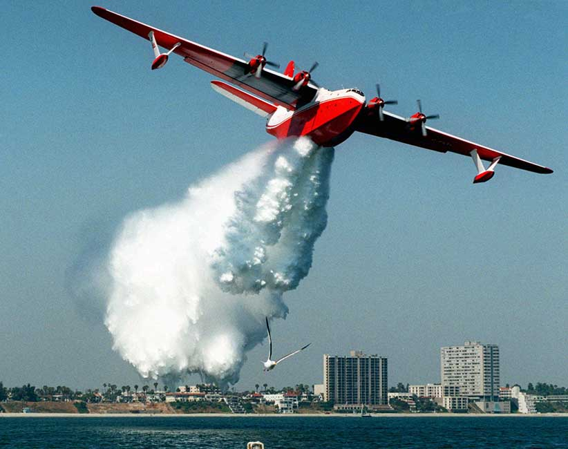 FILE--A Martin Mars flying boat water bomber makes a demonstration drop of some 7,200 gallons of water off the shore of Long Beach, Calif., in this Thursday, June 18, 1998 file photo. Even without a formal request for Canadian help in fighting California's wildfires, the world's largest water bomber will soon be winging its way south while authorities in B.C. are scrambling to see what assets are available if such a call comes in. THE CANADIAN PRESS/AP/Reed Saxon