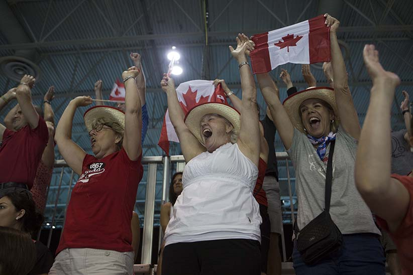 Sandra Purves (left) and Cindy McKelvie celebrate Canada's win over Dominican Republic in men's handball. Purves and McKelvie were part of a group of eight women who play together on a volleyball team in Sarnia and travelled together to Toronto to watch the Pan Am games. Photograph by Della Rollins.
