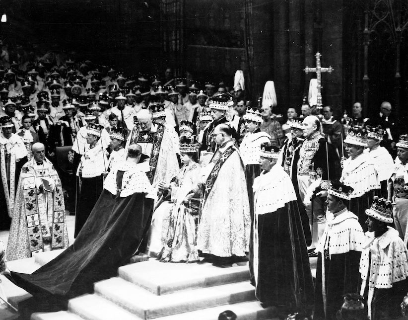 Britain's Prince Philip, the Duke of Edinburgh, kneeling, places his hands between those of his wife, Queen Elizabeth II, as he swears homage, during the Coronation ceremony in Westminster Abbey, in this June 2, 1953 file photo. (AP Photo)
