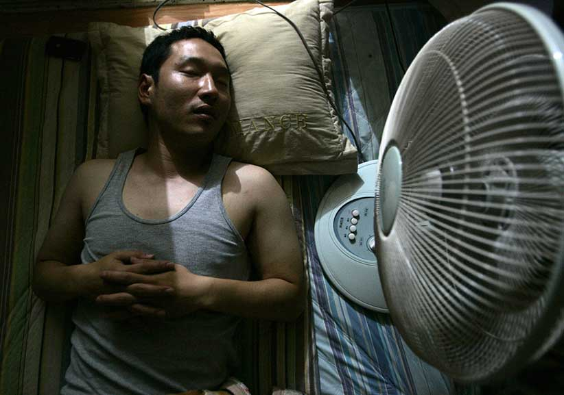 A man lies next to an electric fan in his home in Seoul July 4, 2007. Summertime in South Korea means cold beer on steamy nights and lonely deaths in stuffy rooms blamed on electic fans. Electric fans and Koreans are a deadly combination, according to an urban legend in the country that has it if a person sleeps in a closed room with a fan on all night they may never wake up. (Han Jae-Ho/Reuters)