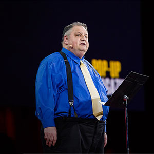 Steve Silberman delivers a speech at a Ted Talk.  Still from YouTube