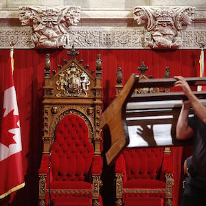 A worker carries a bench while preparing the Senate chamber on Parliament Hill in Ottawa October 10, 2013. Canada's Prime Minister Stephen Harper will outline his government's agenda in the Speech from the Throne on October 16.  (CANADA - Tags: POLITICS) - RTX1469P Chris Wattie/Reuters