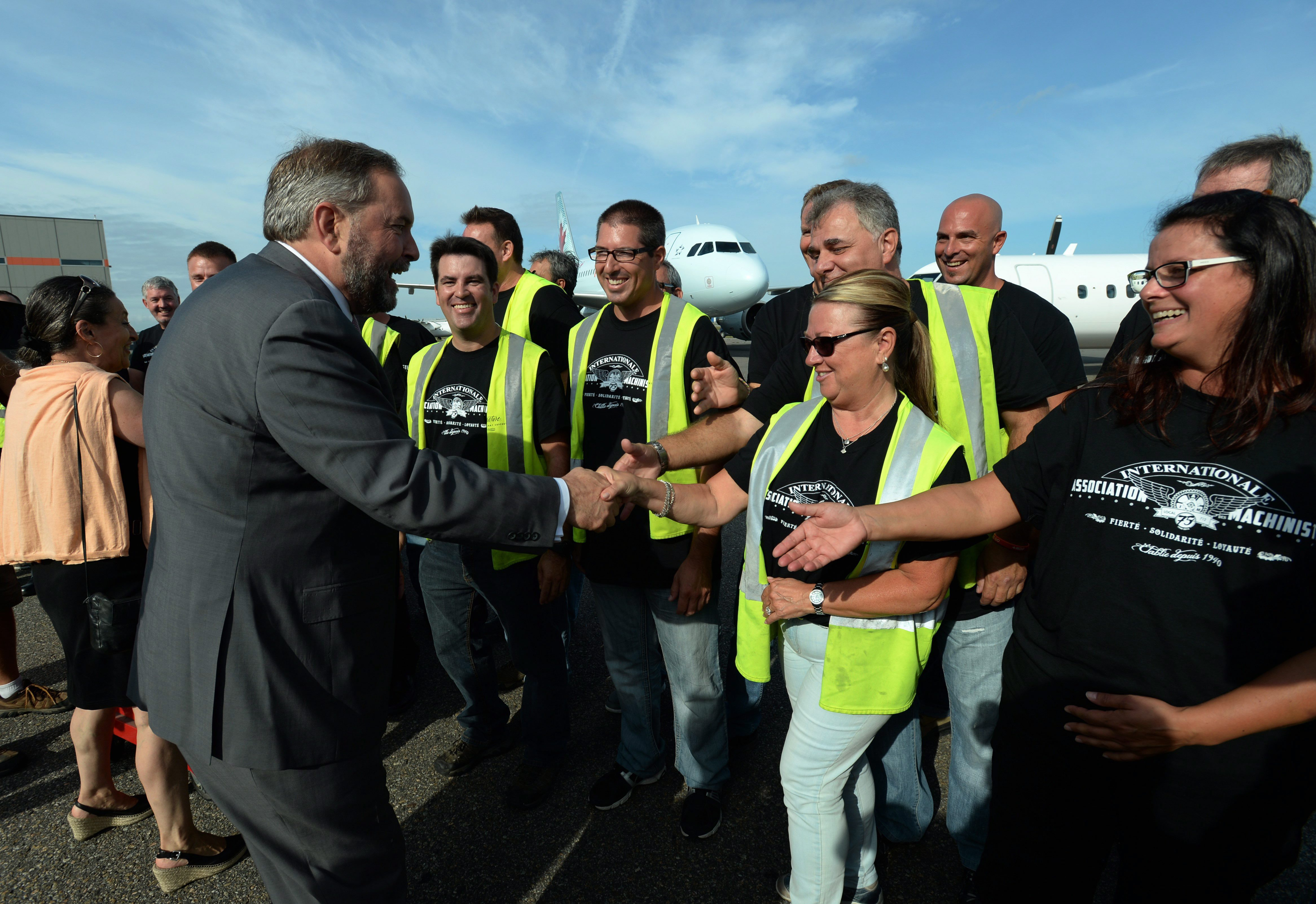 NDP leader Thomas Mulcair shakes hands with aerospace workers as he makes a campaign stop in Montreal on Tuesday, September 8, 2015. THE CANADIAN PRESS/Sean Kilpatrick