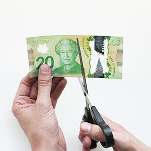 Man cutting a $20 bill in half.  Photograph by May Truong