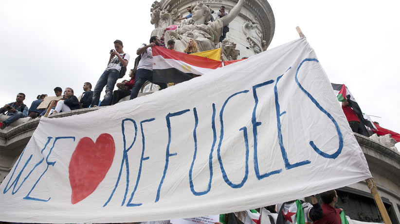"People hold a banner that says ""We love refugees"" as they take part in a demonstration asking for a change in the refugee policy in Europe on the Republique square in Paris, France, September 5, 2015. (Philippe Wojazer/Reuters)"
