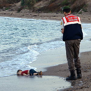 ADDS IDENTIFICATION OF CHILD   Paramilitary police officers investigate the scene before carrying the lifeless body of Aylan Kurdi, 3, after a number of migrants died and a smaller number were reported missing after boats carrying them to the Greek island of Kos capsized, near the Turkish resort of Bodrum early Wednesday, Sept. 2, 2015. The family — Abdullah, his wife Rehan and their two boys, 3-year-old Aylan and 5-year-old Galip — embarked on the perilous boat journey only after their bid to move to Canada was rejected. The tides also washed up the bodies of Rehan and Galip on Turkey's Bodrum peninsula Wednesday, Abdullah survived the tragedy. AP