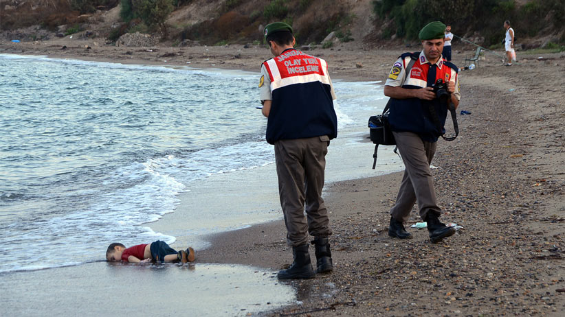 Paramilitary police officers investigate the scene before carrying the lifeless body of Aylan Kurdi, 3, after a number of migrants died and a smaller number were reported missing after boats carrying them to the Greek island of Kos capsized, near the Turkish resort of Bodrum early Wednesday, Sept. 2, 2015. The family — Abdullah, his wife Rehan and their two boys, 3-year-old Aylan and 5-year-old Galip — embarked on the perilous boat journey only after their bid to move to Canada was rejected. The tides also washed up the bodies of Rehan and Galip on Turkey's Bodrum peninsula Wednesday, Abdullah survived the tragedy. AP