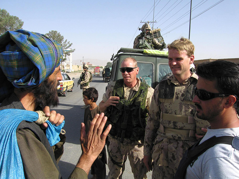 Canada's ambassador to Afghanistan Chris Alexander, second from right, speaks with a resident through an interpreter about Afghanistan's upcoming elections in Kandahar, Afghanistan on Tuesday Aug. 16, 2005. (Terry Pedwell/CP)