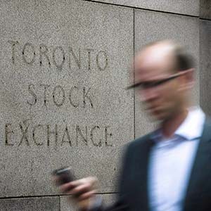 A man walks past a building in Toronto that used to house the Toronto Stock Exchange on August 18 2011. The Toronto stock market looked to open slightly higher as traders digest the latest data on U.S. retail sales and consumer sentiment. (Aaron Vincent Elkaim/CP)