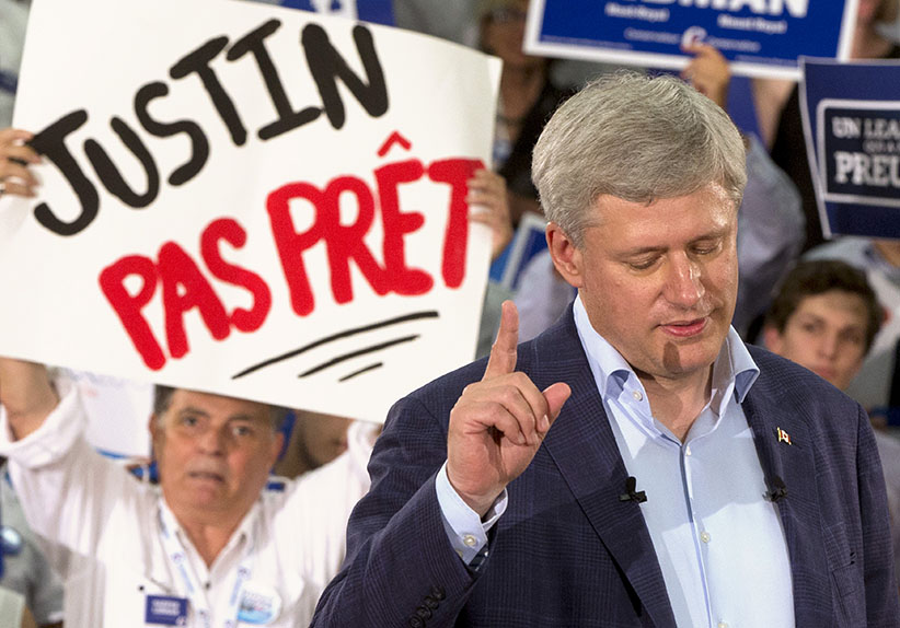 """Canadian Prime Minister Stephen Harper speaks to supporters during a rally in Montreal, Quebec, Canada August 2, 2015. Harper on Sunday called a parliamentary election for Oct 19, kicking off a marathon 11-week campaign, the longest federal election campaign in recent history. The sign reads: """"Justin (Trudeau) not ready"""". (Christinne Muschi/Reuters)"""