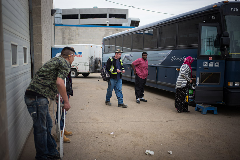 FORT MCMURRAY, CANADA - APRIL 28: Passengers board a coach bus leaving on April 28th, 2015 in Fort McMurray, Canada. Fort McMurray is currently coping with an economic downturn as a result of low oil prices. Most of the layoffs in recent months have affected the transient workforce, prompting many to leave the city in search of work. Canada's oil and gas industry is expected to lose 37% of its revenues in 2015. (Ian Willms/Getty Images)