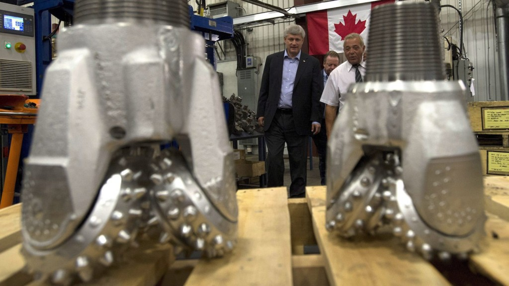 Conservative leader Stephen Harper speaks with Joe Guido, President of Premier Mining Products as he is shown drill bits during a campaign stop in North Bay, Ont., on Wednesday, September 2, 2015. THE CANADIAN PRESS/Adrian Wyld