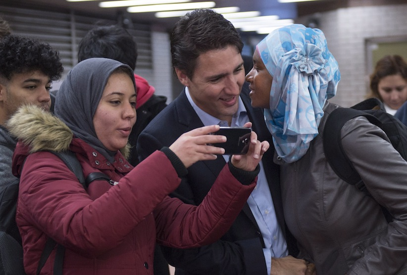 A woman kisses prime minister-designate Justin Trudeau as he greets constituents at a subway station in his riding of Papineau on Tuesday, October 20, 2015, the morning after winning a majority government in the federal election. (Paul Chiasson/CP)