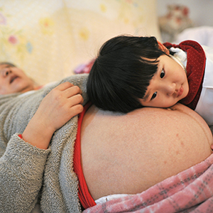 Li Yan (L), pregnant with her second child, lies on a bed as her daughter places her head on her mother's stomach in Hefei, Anhui province February 20, 2014. Li gave birth to a baby boy on February 23, 2014 after Li's family became the first to receive a birth permit to have a second child in the province earlier this month, local media reported. Chinese government said late last year it would allow millions of families to have two children, with a relaxation of its one-child policy if one of the parents was an only child. Picture taken February 20, 2014. REUTERS/China Daily (CHINA - Tags: SOCIETY POLITICS) CHINA OUT. NO COMMERCIAL OR EDITORIAL SALES IN CHINA - RTR3FP4Z
