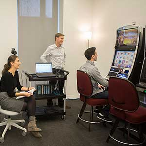 October 2, 2015 - Vancouver: (left to right) Spencer Murch, graduate student in Cognitive Science, Brooke McDonald, an undergraduate research assistant, and Luke Clark, director of the Centre for Gambling Research, watch Mario Ferrari, a graduate student in Clinical Psychology, during an experiment at the Centre for Gambling Research at UBC in Vancouver. (Photograph by Della Rollins)