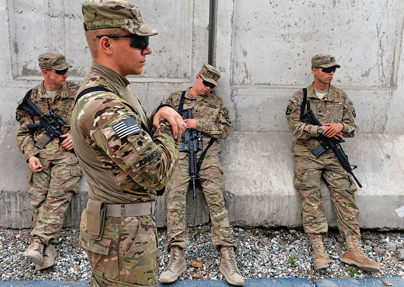 US soldiers of the Combined Team Nangarhar of the CT Bastogne, 1st Brigade Combat Team, 101st Airborne Division (Air Assault) of the United States take a break after an award ceremony at Forward Operating Base, Finley Shields in Jalalabad in Nangarhar province on April 6, 2013. An estimated 100,000 foreign troops have been fighting the Taliban for the past 11 years and are due to leave Afghanistan by December 31, 2014 to be replaced by a smaller contingent to train and advise their local counterparts. (Manjunath Kiran/AFP/Getty Images)