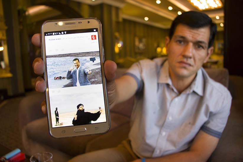 In Erbil, Iraq, Abdullah Kurdi displays one version of the picture of his dead son that he has found on the internet: photoshopped versions showing Syrian President Bashar al Assad and Abu Bakr al Baghdadi, the leader of Islamic State, taking a selfie.   (Photograph by Adnan Khan)