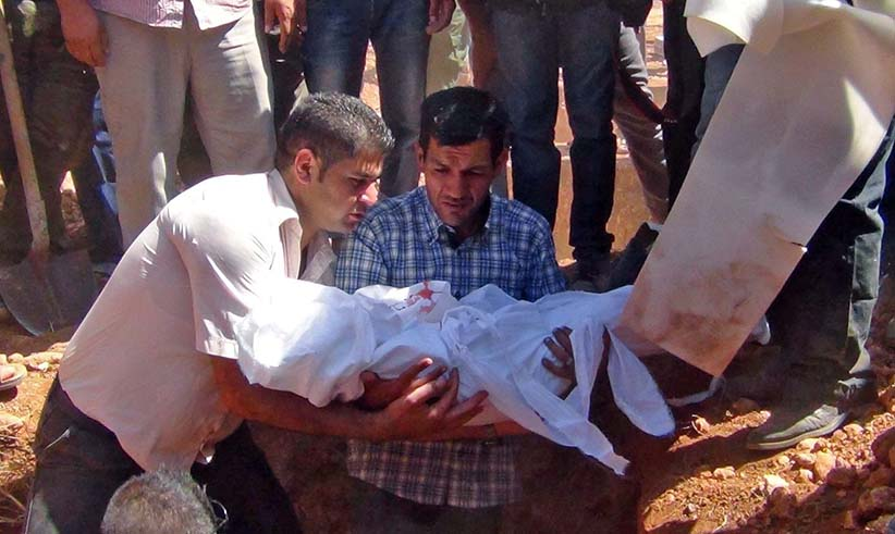 Abdullah al-Kurdi holds his son's body as they bury drowned migrants during a funeral in Kobani, Syria. (DICLE NEWS AGENCY/EPA/CP)
