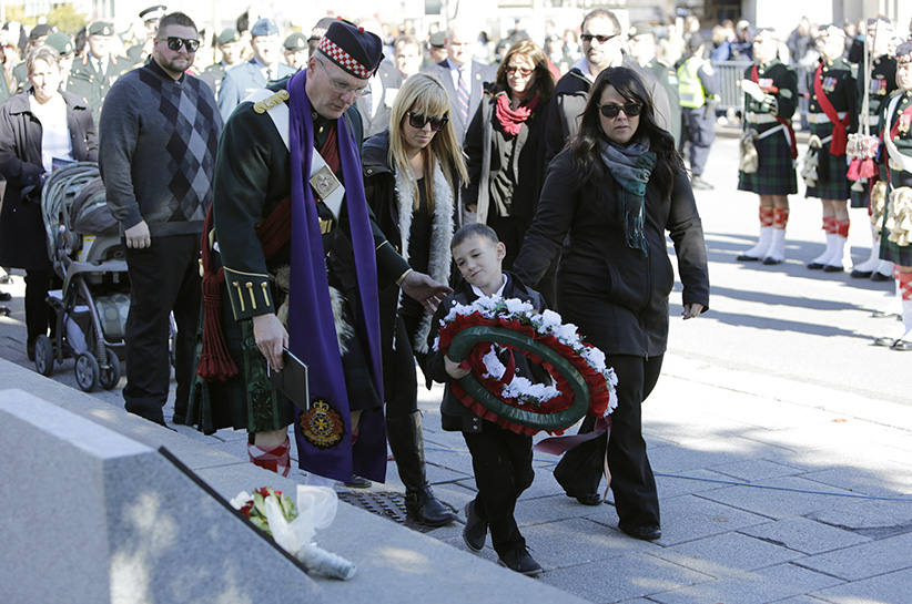 Marcus Cirillo lays a wreath in front of the plaque dedicated to his father after the commemoration ceremony to mark one year since the fatal Oct. 22, 2014 shooting of Cpl. Nathan Cirillo, at the National War Memorial in Ottawa on Oct. 22, 2015. (Photograph by David Kawai)