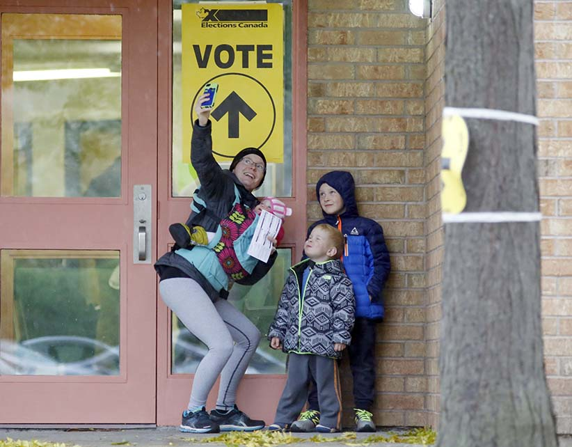 Alexandra Pettit takes a selfie with her kids at the Gloucester Presbyterian Church polling station, in Ottawa, after casting her vote in the Canadian federal election on Monday, Oct. 19, 2015. (PATRICK DOYLE/CP)