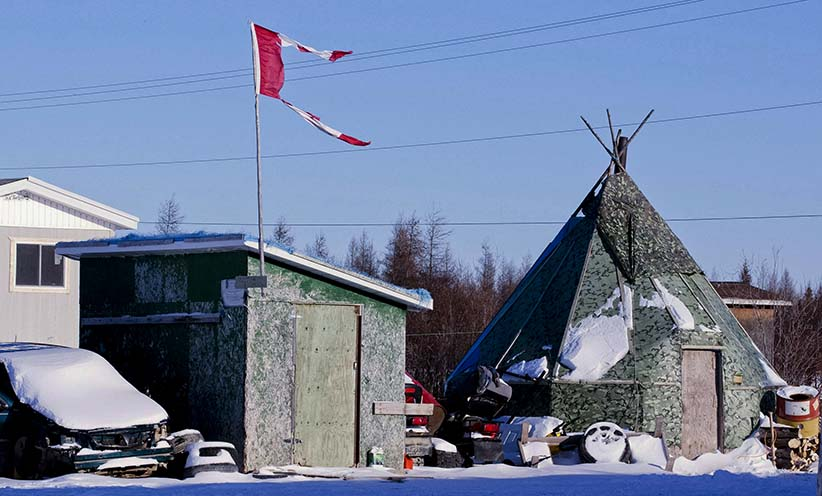 The remains of a Canadian flag can be seen flying over a building in Attawapiskat, Ont. on  November 29, 2011. The federal government is forcing the troubled Attawapiskat First Nation to pay a private-sector consultant about $1,300 a day to run its finances - even though the government's own assessments say the third-party management system is not cost-effective. (Adrian Wyld/CP)
