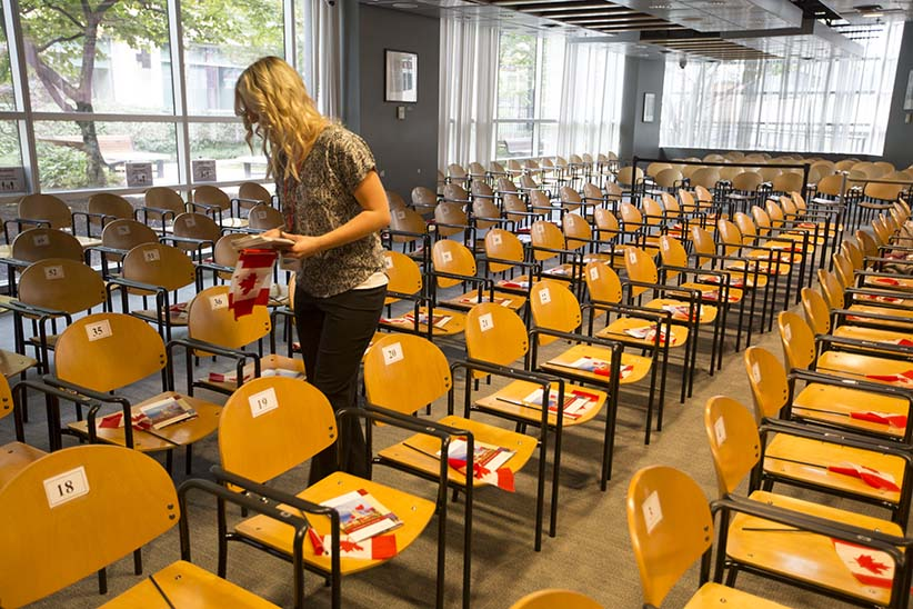 OCT 6 2015--Vancouver BC--Citizenship ceremony: A woman places flags and programs on chairs in preparation for a citizenship ceremony in Vancouver. (PHOTOGRAPH BY BRIAN HOWELL)