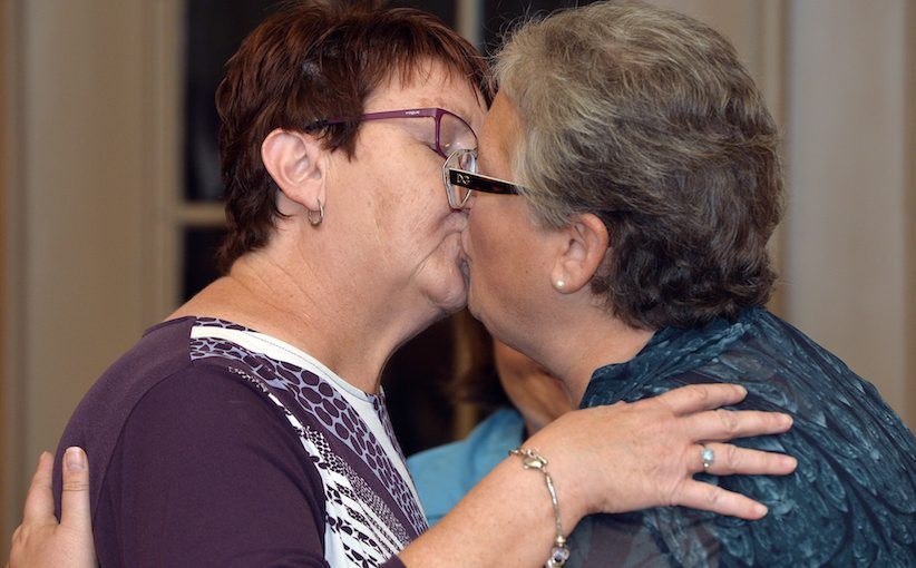 Karen Roberts, left, and April Miller kiss after renewing their vows in a public ceremony, Saturday, Oct. 24, 2015, in Morehead, Ky. Miller and Roberts were the plaintiffs in a suit filed against Rowan County Clerk Kim Davis by the American Civil Liberties Union in an attempt to have her office issue marriage licenses. (AP Photo/Timothy D. Easley)