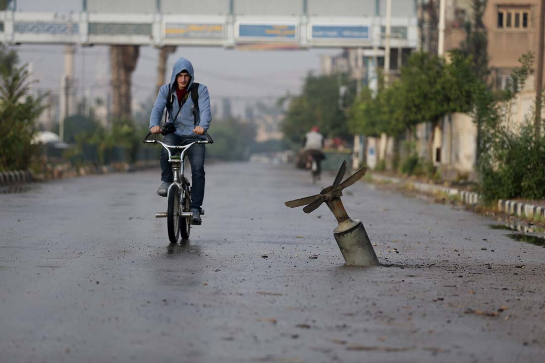 A resident rides his bicycle near what activists said was an  exploded cluster bomb shell in the town of Douma, eastern Ghouta in Damascus November 5, 2015. (Bassam Khabieh/Reuters)