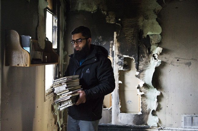 Usama Zahid removes the Quran and other books from shelves, on Sunday, Nov. 15, 2015, as congregation members clean up debris after the only mosque in Peterborough, Ont., was deliberately set on fire last night. (Christopher Katsarov/CP)