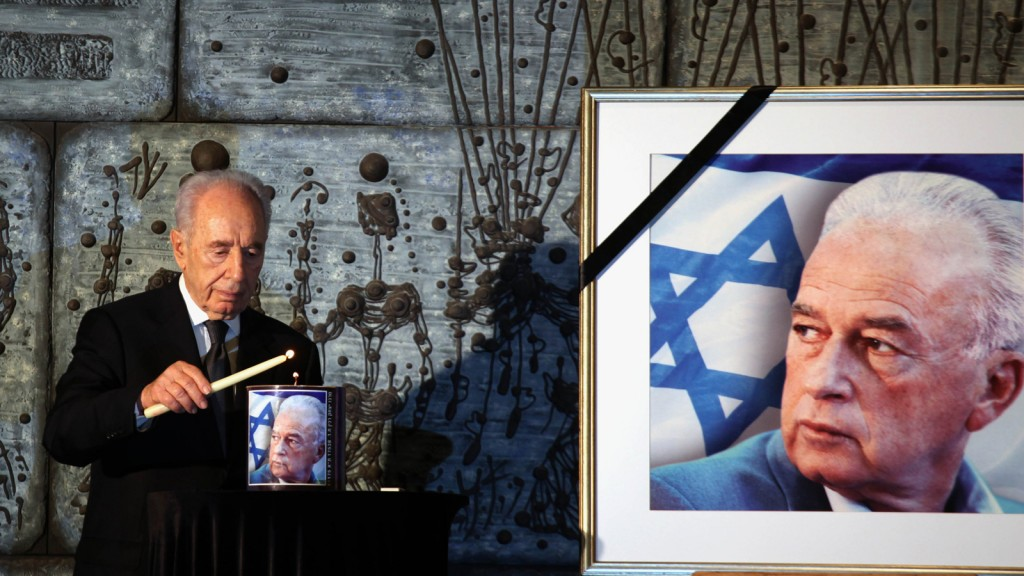 Israeli President Shimon Peres lights a candle during a memorial service in memory of the late Israeli prime minister Yitzak Rabin (portrait R) in Jerusalem on November 08, 2011. (Gali Tibbon/AFP/Getty Images)
