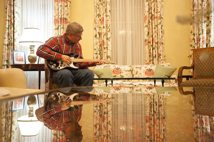 Prime Minister Stephen Harper plays guitar in the living room at 24 Sussex on the evening of February 18th, 2011. (Jason Ransom)