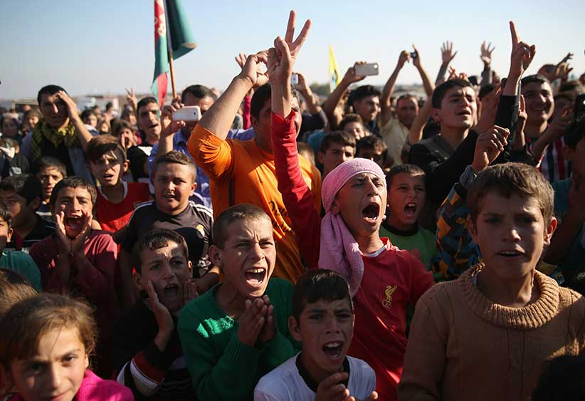 Yazidi refugees celebrate news of the liberation of their homeland of Sinjar from ISIL extremists, while at a refugee camp on November 13, 2015 in Derek, Rojava, Syria. Kurdish Peshmerga forces in Iraq say they have retaken Sinjar, with the help of airstrikes from U.S. led coalition warplanes. The Islamic State captured Sinjar in August 2014, killing many and sexually enslaving thousands of Yazidi women. (John Moore/Getty Images)