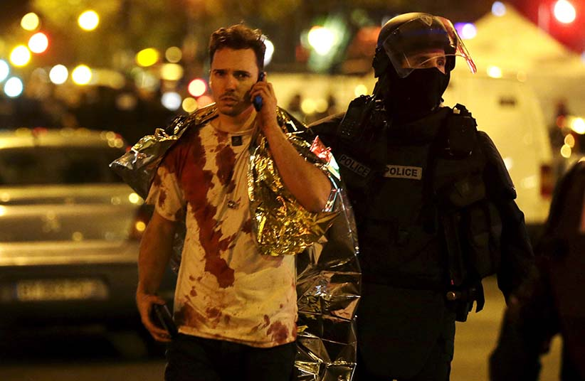 ATTENTION EDITORS - VISUAL COVERAGE OF SCENES OF INJURY     A French policeman assists a blood-covered victim near the Bataclan concert hall following attacks in Paris, France, November 14, 2015. Gunmen and bombers attacked busy restaurants, bars and a concert hall at locations around Paris on Friday evening, killing dozens of people in what a shaken French President described as an unprecedented terrorist attack (Philippe Wojazer/Reuters)
