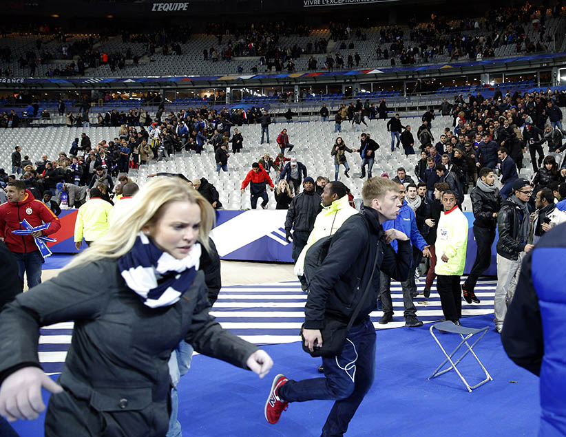 Spectators invade the pitch of the Stade de France stadium after the international friendly soccer match between France and Germany in Saint Denis, outside Paris, Friday, Nov. 13, 2015. Hundreds of people spilled onto the field of the Stade de France stadium after explosions were heard nearby during a friendly match between the French and German national soccer teams. French President Francois Hollande says he is closing the country's borders and declaring a state of emergency after several dozen people were killed in a series of unprecedented terrorist attacks.  (Christophe Ena/AP)