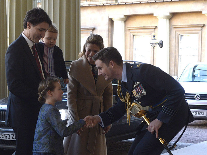 Queen's equerry Wing Cmdr. Sam Fletcher, right, shakes hands with Ella-Grace Trudeau as he greets Canadian Prime Minister Justin Trudeau, left, his wife Sophie Gregoire-Trudeau, and son Hadrien in London on Wednesday, Nov. 25, 2015. (Adrian Wyld/CP)