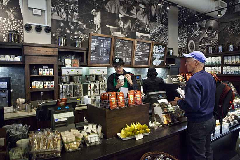 A customer purchases coffee at a newly redesigned Starbucks store in New York City, on Friday, October 29, 2010. Starbucks has committed to have all of its new company-owned stores LEED certified by the end of 2010. (Ramin Talaie/Corbis)