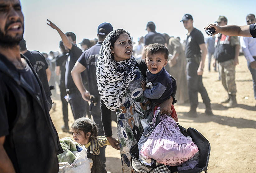 A Syrian Kurdish woman crosses the border between Syria and Turkey at the southeastern town of Suruc in Sanliurfa province on September 23, 2014. The UN refugee agency warned Tuesday that as many as 400,000 people may flee to Turkey from Syria's Kurdish region to escape attacks by the Islamic State group.  (BULENT KILIC/AFP/Getty Images)